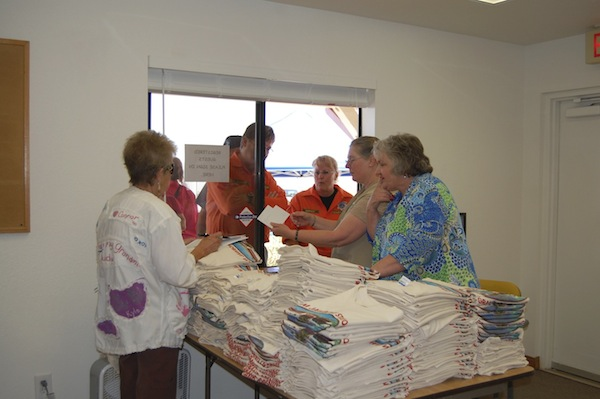 Michelle Williamson, Judy Hogg, and Robin Mallow hand out T-shirts.